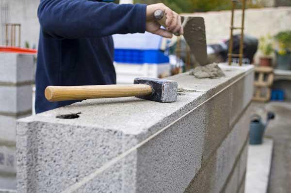 Maçon entrain de monter un mur en parpaing